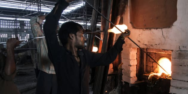 Glassmiths use punties to gather molten glass from the furnace at the Kohinoor Bangle Industries factory in Ferozabad, Uttar Pradesh, India, on Saturday, Feb. 21, 2015. Prime Minister Narendra Modi wants India's companies to embrace their homeland as a manufacturing base. As part of a policy initiative called 'Make in India,' Modi plans to raise the share of manufacturing in the economy to 25 percent by 2022 from 18 percent now. Photographer: Udit Kulshrestha/Bloomberg via Getty Images
