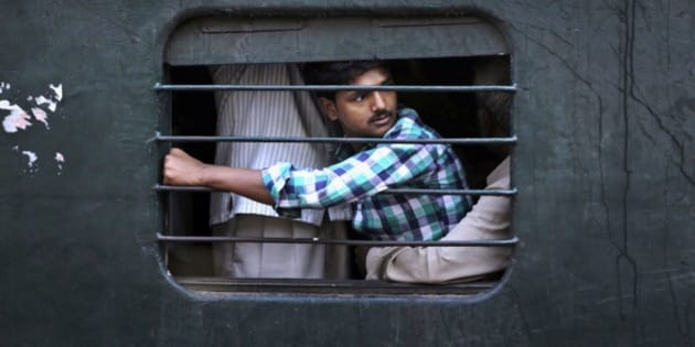 An Indian passenger sits on the lap of another man as he travels in a crowded local train on the outskirts of Kolkata, India, Thursday, Feb. 26, 2015. Indian Railway minister Suresh Prabhu will unveil the Rail Budget 2015 on Thursday for one of the world's largest railways systems that serves more than 23 million passengers a day. (AP Photo/Bikas Das)