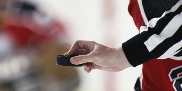 Hockey referee poised to put puck into play, close-up