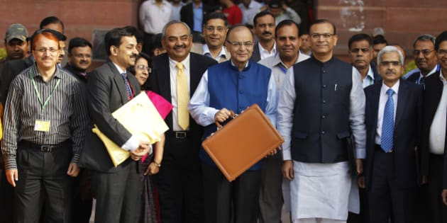 Indian Finance Minister Arun Jaitley, center in blue jacket, display a briefcase containing union budget for the year 2015-16 as he leaves his office for Parliament to present the union budget in New Delhi, India, Saturday, Feb. 28, 2015. (AP Photo/Altaf Qadri)