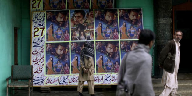 In this Sunday, April 29, 2012 photo, a Pakistani man looks at a board displayed on it advertisements of a local movie, outside Taj Mahal cinema in Abbottabad, Pakistan. One year since U.S. commandos flew into this army town and killed Osama bin Laden, Pakistan has tried to close one of the most notorious chapters in its history. The compound that housed him for six years was razed to the ground, and the wives and children who shared the hideaway were flown to Saudi Arabia just last week. (AP Photo/Muhammed Muheisen)