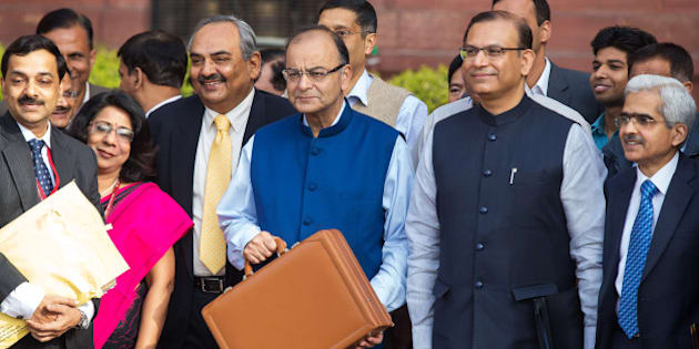 Arun Jaitley, India's finance minister, third right, Rajiv Mehrishi, finance secretary, third left, Jayant Sinha, junior finance minister, second right, and other members of the finance ministry stand for a photograph outside the North Block of the Central Secretariat building before leaving to table the budget in parliament in New Delhi, India, on Saturday, Feb. 28, 2015. Prime Minister Narendra Modi diverged from a previously announced path to narrow India's budget deficit in an effort to spur faster growth in Asias third-biggest economy. Photographer: Graham Crouch/Bloomberg via Getty Images