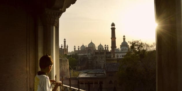 Child staring at Badshahi Mosque, Lahore from Lahore Fort at sunset. Both of the buildings are artistic marvels of Mughal Empire.