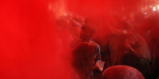 VRINDAVAN, INDIA - FEBRUARY 27: Hindu devotees smeared in colors during Lathmar Holi celebrations at Barsana, Uttar Pradesh, on February 28, 2015 in Vrindavan, India. During Lathmar Holi the women of Barsana beat the men from Nandgaon, the hometown of Lord Krishna, with wooden sticks in response to their teasing. (Photo by Burhaan Kinu/Hindustan Times via Getty Images)