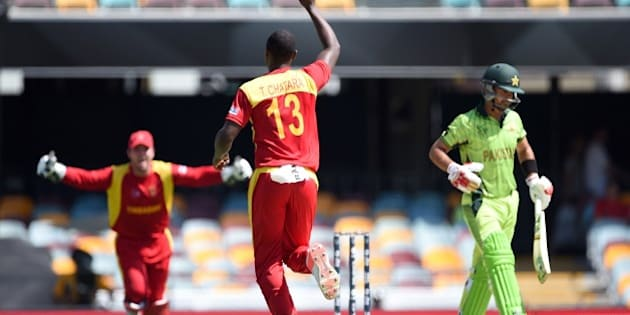 Zimbabwe bowler Tendai Chatara (C) celebrates after taking the wicket of Pakistan cricketer Ahmed Shehzad (R) during the 2015 Cricket World Cup Pool B match between Pakistan and Zimbabwe at the Gabba Stadium in Brisbane on March 1, 2015.  AFP PHOTO / INDRANIL MUKHERJEE   -- IMAGE RESTRICTED TO EDITORIAL USE - STRICTLY NO COMMERCIAL USE--        (Photo credit should read INDRANIL MUKHERJEE/AFP/Getty Images)