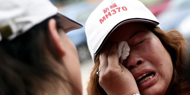A relative of Chinese passengers from the missing Malaysia Airlines flight MH370 is consoled as she breaks down during a protest outside the Malaysia Airlines office in Subang on the outskirts of Kuala Lumpur on February 12, 2015. Chinese relatives of those on board missing Malaysia Airlines flight MH370 protested outside the carrier's office on February 12, demanding Malaysia withdraw a statement declaring all the passengers dead.  AFP PHOTO / MANAN VATSYAYANA        (Photo credit should read MANAN VATSYAYANA/AFP/Getty Images)