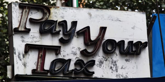 A sign reading 'Pay  Your Tax' sits outside the income tax office in Kolkata, India, on Monday, March 14, 2011. India faces pressure to step up its battle against price gains even after the steepest interest-rate increases among Asia's major economies, as oil costs rise and consumer demand strengthens. Photographer: Brent Lewin/Bloomberg via Getty Images