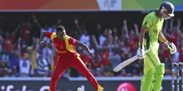 Zimbabwe's Tawanda Mupariwa, left, celebrates the wicket of Pakistan's Sohaib Maqsood during the Pool B Cricket World Cup match in Brisbane, Australia, Sunday, March 1, 2015. (AP Photo/Tertius Pickard)
