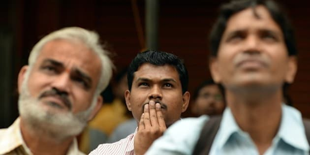 Indian bystanders watch a digital screen showing Indian Finance Minister Arun Jaitley delivering his Budget speech at Parliament in New Delhi, at the Bombay Stock Exchange (BSE) in Mumbai on February 28, 2015. India's finance minister pledged major investment in infrastructure, saying it was time for the economy to 'fly', as he unveiled the new right-wing government's first full budget.  AFP PHOTO / PUNIT PARANJPE        (Photo credit should read PUNIT PARANJPE/AFP/Getty Images)