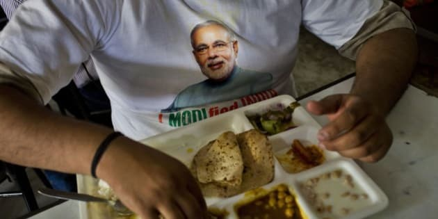 "A supporter wears a t-shirt with a portrait of Bharatiya Janata Party (BJP) leader and India's next prime minister Narendra Modi and eats a meal at the canteen of the BJP party office in New Delhi, Friday, May 16, 2014. Modi and his party won national elections in a landslide Friday, preliminary results showed, driving the long-dominant Congress party out of power in the most commanding victory India has seen in more than a quarter century. Writing on banner reads ""Good days are ahead."" (AP Photo/Bernat Armangue)"