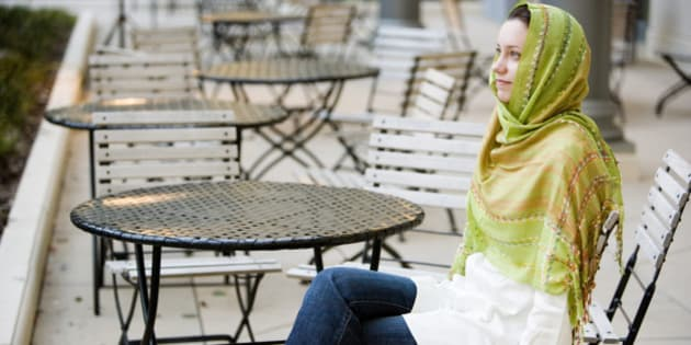 woman wearing a head scarf sitting at a table