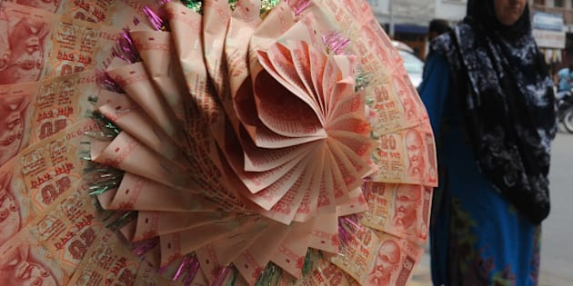 A Kashmiri pedestrian walks past a stall selling wedding garlands made from Indian rupee notes at a market in Srinagar on August 28, 2013. India's rupee slumped nearly four percent to a fresh record low against the dollar as concerns about a US-led military strike against Syria compounded deepening domestic economic woes. The Indian unit, which lost three percent on Tuesday, was down 2.46 percent at 67.87 rupees to the dollar in afternoon trade after plunging 3.84 percent at one point to 68.74 rupees.  AFP PHOTO/ Rouf BHAT        (Photo credit should read ROUF BHAT/AFP/Getty Images)