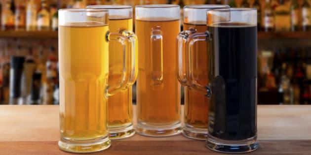 beer flight of five sampling mugs of light and dark craft beer in a bar