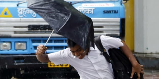 An Indian school boy jumps over a puddle of water as it rains in Mumbai, India, Wednesday, July 2, 2014. Heavy rains lashed the city, disrupting traffic and causing waterlogging in several areas. (AP Photo/Rajanish Kakade)