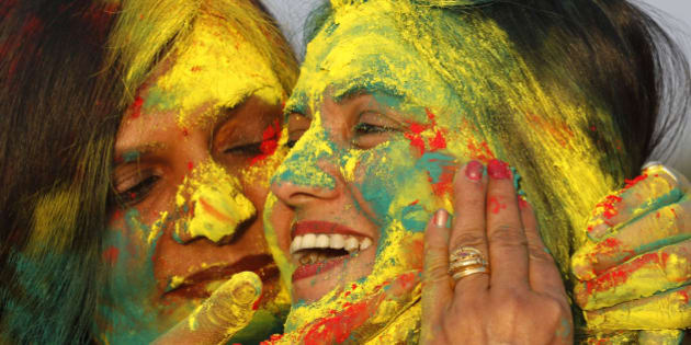"Indian women smear colors on their faces as they celebrate ""Holi,"" a festival of colors, in Allahabad, India, Sunday, March 16, 2014. The festival heralds the arrival of spring. (AP Photo/Rajesh Kumar Singh)"