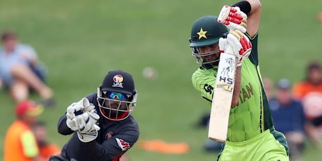 Pakistan's Ahmed Shehzad (R) plays a shot as United Arab Emirates wicketkeeper Swapnil Patil (L) looks on during the Pool B Cricket World Cup match between the United Arab Emirates (UAE) and Pakistan at McLean Park in Napier on March 4, 2015.      AFP PHOTO / Michael Bradley        (Photo credit should read MICHAEL BRADLEY/AFP/Getty Images)