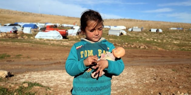 MOSUL, IRAQ - MARCH 2: An Ezidi child holds her doll outskirts of Sinjar mountain, Mosul, on March 2, 2015. Ezidis fled from Daesh (Islamic State of Iraq and Levant) attacks shelter in Sinjar Mountain and live under harsh conditions with their family. (Photo by Emrah Yorulmaz/Anadolu Agency/Getty Images)