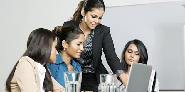 Indian women business colleagues working around a laptop