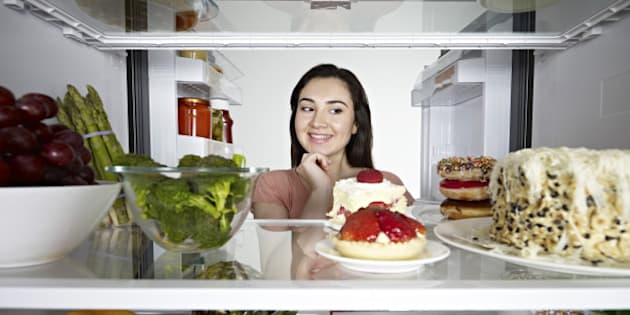 Woman looking at cake in through the fridge.