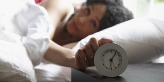 Black woman turning of alarm clock