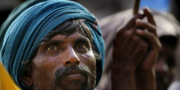 A tribal man whose land is being acquired by government participates in a protest with others against the proposed bills to amend land acquisition and rehabilitation laws, in New Delhi, India, Thursday, July 23, 2009. (AP Photo/ Manish Swarup)