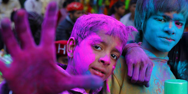 NEW DELHI, INDIA - MARCH 4: Indian children, smeared with gulal-coloured powder, smiles at the camera during Holi celebrations on March 4, 2015 in New Delhi, India. Festival of colors, fun and frolic Holi bridges the social gap and renew sweet relationships. It is also called Fagun, Vasant Utsav or spring festival as it falls on Phalgun Purnima which comes in February end or early March. (Photo Raj K Raj/Hindustan Times via Getty Images)