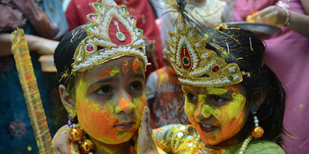 Indian children dressed as Lord Krishna (L) and Radha play with coloured powder during a Holi celebration at a temple in Amritsar on March 26, 2013.  Holi, also called the Festival of Colours, is a popular Hindu spring festival observed in India at the end of the winter season on the last full moon day of the lunar month and falls on March 27 this year.  AFP PHOTO/ NARINDER NANU        (Photo credit should read NARINDER NANU/AFP/Getty Images)