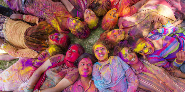 Young Indian people celebrating the Hindu festival of Holi by throwing coloured powder called Gulal at each other