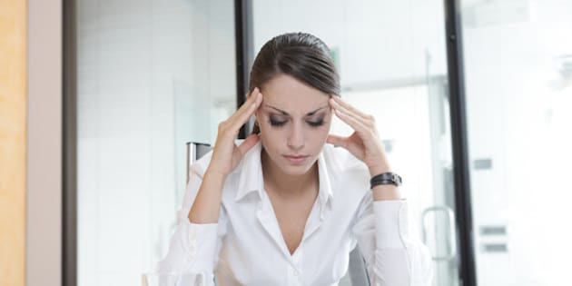 Overworking business woman suffering from headache