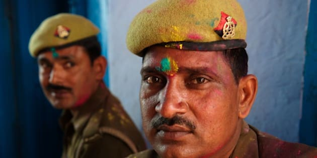 BARSANA, UTTAR PRADESH, INDIA - 2013/03/21: Even policemen can't quite escape the colours of Holi. Revellers gather at the Shriji Temple (Laadli Sarkar Mahal), during Lathmar Holi, smeared with coloured powder. It is held during a full moon and the town becomes swamped with tourists and revellers making the pilgrimage for a glimpse of 'God', the Lord Shiva, who is revealed inside the temple only fleetingly.. (Photo by Jeremy Horner/LightRocket via Getty Images)