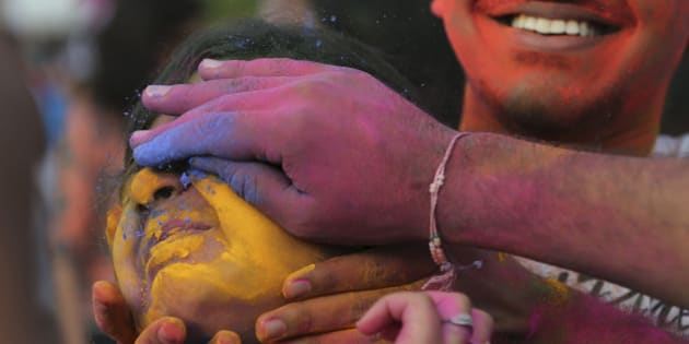 Participants place colored powder on a woman's face as they join celebrations of the Holi festival in suburban Pasay, south of Manila, Philippines, on Sunday, March 1, 2015. The event is led by Indian nationals as they mark Holi, a Hindu spring festival also known as festival of colors. (AP Photo/Aaron Favila)