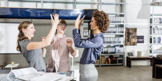 Businesswomen cheering in office