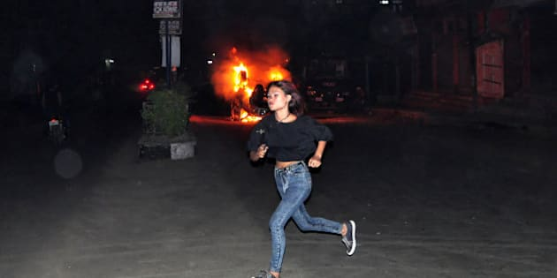 In this Thursday, March 5, 2015 photo, an unidentified girl runs in front of a car set on fire by a mob, during clashes with police following the lynching of a man accused of rape in Dimapur, India, in the northeastern Indian state of Nagaland. Several thousand people overpowered security at Dimapur Central Prison in Nagaland on Thursday, where they dragged away a man accused of rape and then lynched him, police said Friday. (AP Photo/Imojen I Jamir)