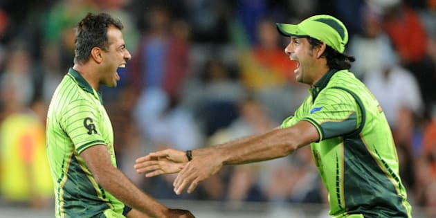 Pakistan's Wahab Riaz, left, runs to his teammate Mohammad Irfan as they celebrate their 29 run win over South Africa in their Cricket World Cup Pool B match in Auckland, New Zealand, Saturday, March 7, 2015. (AP Photo/Ross Setford)
