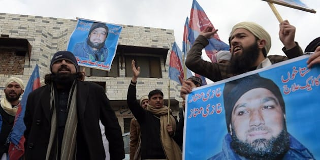 Pakistani Islamist and supporters of former police bodyguard Mumtaz Qadri, hold his portrait as they shout slogans calling for his release during a protest outside the high court building in Islamabad on February 3, 2015.  A former Pakistan police bodyguard appealed February 3 against his death sentence for murdering a provincial governor who sought reform of blasphemy laws, as hundreds rallied outside the court to show support.    AFP PHOTO / Aamir QURESHI        (Photo credit should read AAMIR QURESHI/AFP/Getty Images)
