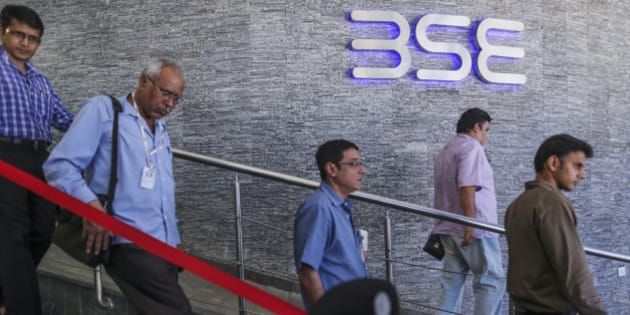 People walk past the Bombay Stock Exchange (BSE) logo displayed outside the building's lobby in Mumbai, India, on Tuesday, Aug. 5, 2014. Indias benchmark stock-index fell as lenders declined after the central bank said curbing prices will create the best conditions for economic growth even as it left interest rates unchanged. Photographer: Dhiraj Singh/Bloomberg via Getty Images