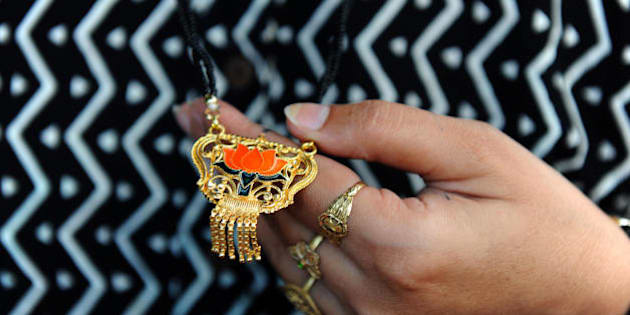 An unidentified Indian married woman admires a mangalsutra made of brass and featuring the symbol of the Bharatiya Janta Party (BJP) for sale on the stall of electoral publicity dealer Prakashbhai Naik in Ahmedabad on April 15, 2009.   Naik sells Mangalsutra at Indian Rupees 25 (US 50 cents) each.  A mangalsutra is an Indian symbol of Hindu marriage, consisting of a gold ornament strung from a yellow thread, a string of black beads or a gold chain. It is comparable to a Western wedding ring, and is worn by a married woman until her husband's death. As many as 5,000 mangalsutras, made of brass, will be distributed in each of the 26 electoral constituencies in the westenr Indian state of Gujarat. India will hold its fifteenth parliamentary general elections in five phases on April 16, April 23, April 30, May 7,and May 13 and the new parliament will be constituted before June 2.  AFP PHOTO/ Sam PANTHAKY (Photo credit should read SAM PANTHAKY/AFP/Getty Images)