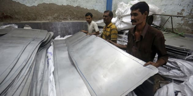 Workers pick up a sheet of stainless steel inside a manufacturing workshop in the suburb of Mira-Bhayander in Thane, Maharashtra, India, on Tuesday, Jan. 7, 2014. Tata Steel Ltd. and Steel Authority of India Ltd., the nations biggest producers, are set to report their smallest profit margins in more than a decade as demand increases at the slowest pace since the global recession. Photographer: Vivek Prakash/Bloomberg via Getty Images