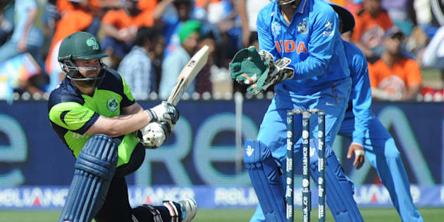 Ireland's Paul Stirling plays a sweep shot as India's wicketkeeper MS Dhoni watches during their Cricket World Cup Pool B match in Hamilton, New Zealand, Tuesday, March 10, 2015. (AP Photo/Ross Setford)