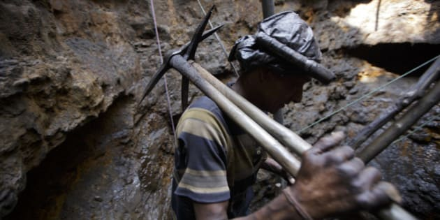 MEGHALAYA, INDIA- APRIL 30:  A coal miner walks out of a mine in Jaintia Hills, Meghalaya in India on April 30, 2014. Indian government announced in September that it would double the coal production to one billion tons over the next four years to ease the ongoing power shortages. (Photo by Kuni Takahashi/Getty Images)