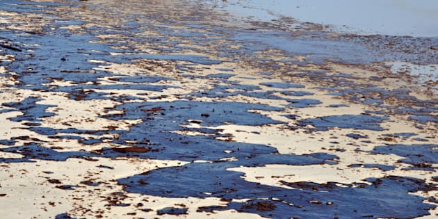 Oil spill on beach with oil skimmers in background.