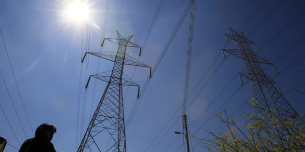 A motorcyclist drives under pylons with high voltage electricity cables passing over houses in northern Athens, Friday, Sept. 16, 2011. The Greek government announced it would impose an additional tax on all property owners in the country. The tax will be collected through electricity bills. Those who do not pay risk having their power cut off. (AP Photo/Thanassis Stavrakis)