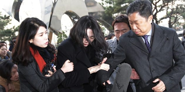 """Cho Hyun-ah, center, former vice president of Korean Air Lines, arrives at the Seoul Western District Prosecutors Office in Seoul, South Korea, Tuesday, Dec. 30, 2014.  A Seoul court is expected to decide Tuesday whether to issue an arrest warrant for Cho, who resigned as vice president at the airline earlier this month amid mounting public criticism over the incident that she forced a flight to return over a bag of macadamia nuts and a current executive for attempts to cover up the """"nut rage"""" case.(AP Photo/Ahn Young-joon)"""