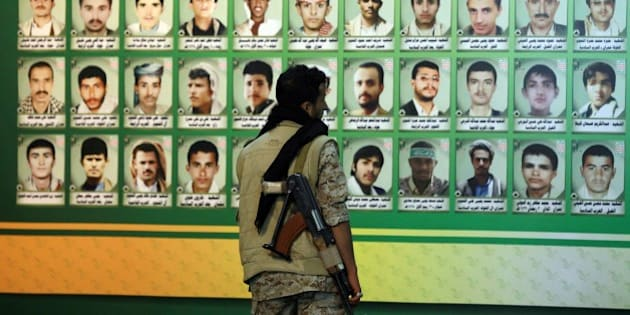 A Huthi militiaman looks at a wall bearing the portraits of 'martyrs', who were reportedly killed during the six-year conflict in the northern Yemeni province of Saada between the Shiite Muslim movement and government forces, during a memorial event in the capital Sanaa on March 5, 2015. Saada has been the scene of a brutal conflict which began in 2004 until 2011 between Yemeni government forces and the Zaidi rebels that has resulted in thousands of casualties which ended with the uprising that forced out president Ali Abdullah Saleh. AFP PHOTO / MOHAMMED HUWAIS        (Photo credit should read MOHAMMED HUWAIS/AFP/Getty Images)