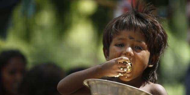 An Indian homeless child eats rice on a roadside in Allahabad, India, Friday, July 5, 2013. The Indian government on Wednesday decided to come out with an ordinance to give two-third of the nation's population the right to 5 kilograms of food grains every month at a highly subsidized rate of 1-3 rupees per kilogram ($0.016- 0.05). If implemented, the country's food security program will be the largest in the world. (AP Photo/ Rajesh Kumar Singh)