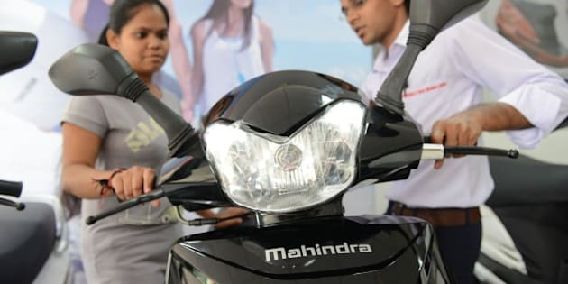 A picture taken on October 8, 2014 shows a woman (L) looking at the recently launched Mahindra Gusto scooter at a Mahindra Two Wheelers Authorised Showroom in Ahmedabad. Mahindra Two Wheelers, a part of USD 16.5-billion Mahindra Group, has entered into a binding bid to acquire 51 percent stake for Rs216 crore, or 28 million, in Peugeot Motorcycles, an affiliate of the 54-billion PSA group.  AFP PHOTO / Sam PANTHAKY        (Photo credit should read SAM PANTHAKY/AFP/Getty Images)