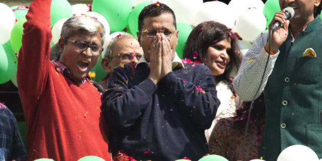 FILE - In this Tuesday, Feb. 10, 2015 file photo, Aam Aadmi Party, or Common Man's Party leader Arvind Kejriwal, center, coughs while the party's senior leader Ashutosh, left, and others shout slogans to celebrate the party's election performance in New Delhi, India. Kejriwal, the former tax official with the chronic cough and the ill-fitting sweaters, the man who had remade himself into a champion for clean government, seemed lost in the political wilderness. The crusading politician was suddenly a punchline. But on Wednesday, Feb. 11, there was Kejriwal on the front page of nearly every Indian newspaper, celebrating election results that again make him New Delhi's chief minister. Kejriwal and the party he created routed the country's best-funded and best-organized political machine and dealt an embarrassing blow to Prime Minister Narendra Modi. (AP Photo/Manish Swarup, File)