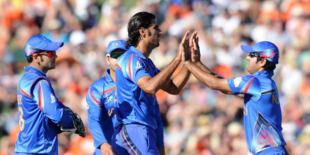 Afghanistan bowler Shapoor Zadran, centre, is congratulated by teammates after dismissing New Zealand's Kane Williamson during their Cricket World Cup Pool A match in Napier, New Zealand, Sunday, March 8, 2015. (AP Photo/Ross Setford)