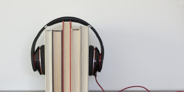 Headphones around a group of books to suggest the concept of listening to audios books.