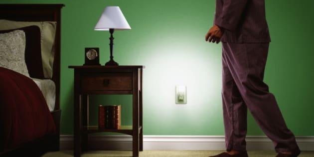 Man wearing pajamas, walking towards bed, low section